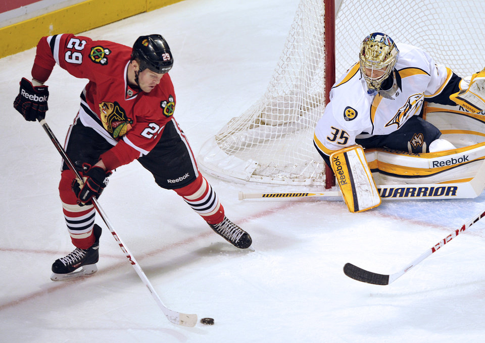 Photo - Chicago Blackhawks' Bryan Bickell (29) looks to shoot the puck on Nashville Predators' Pekka Rinne (35) during the first period of an NHL hockey game Monday, April 1, 2013, in Chicago. (AP Photo/Jim Prisching)