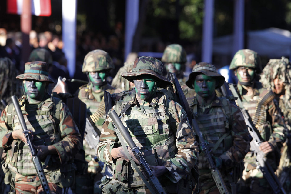 Photo - In this Aug. 15, 2013 photo, Paraguayans soldiers march in full camouflage in a military parade to mark the inauguration of President Horacio Cartes, in Asuncion, Paraguay. Cartes wants open-ended, blanket approval to send troops to the northern department of San Pedro against the Paraguayan People's Army without having to declare a state of emergency. The government blames the guerrilla group for the recent deaths of five farmhands. Human rights groups fear the step, but Cartes has plenty of support. House approval was expected Wednesday night, Aug. 21, 2013, before a Senate vote Thursday afternoon. (AP Photo/ Cesar Olmedo)