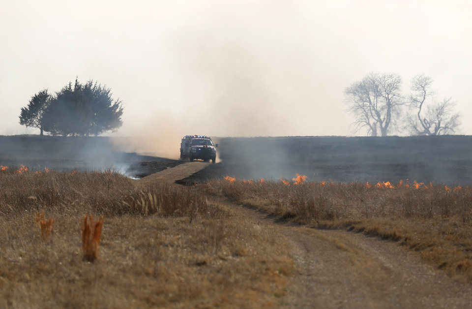 Photo - A firetruck drives in a field near SE 134th as wildfire burns in the area in southeast Oklahoma City, Okla., Sunday, Feb. 12, 2017. Photo by Sarah Phipps, The Oklahoman