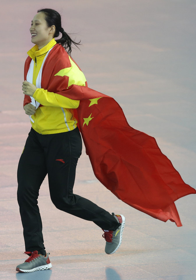 Photo - Gold medallist China's Zang Hong runs holding her national flag after the women's 1,000-meter speedskating race at the Adler Arena Skating Center during the 2014 Winter Olympics in Sochi, Russia, Thursday, Feb. 13, 2014. (AP Photo/Patrick Semansky)