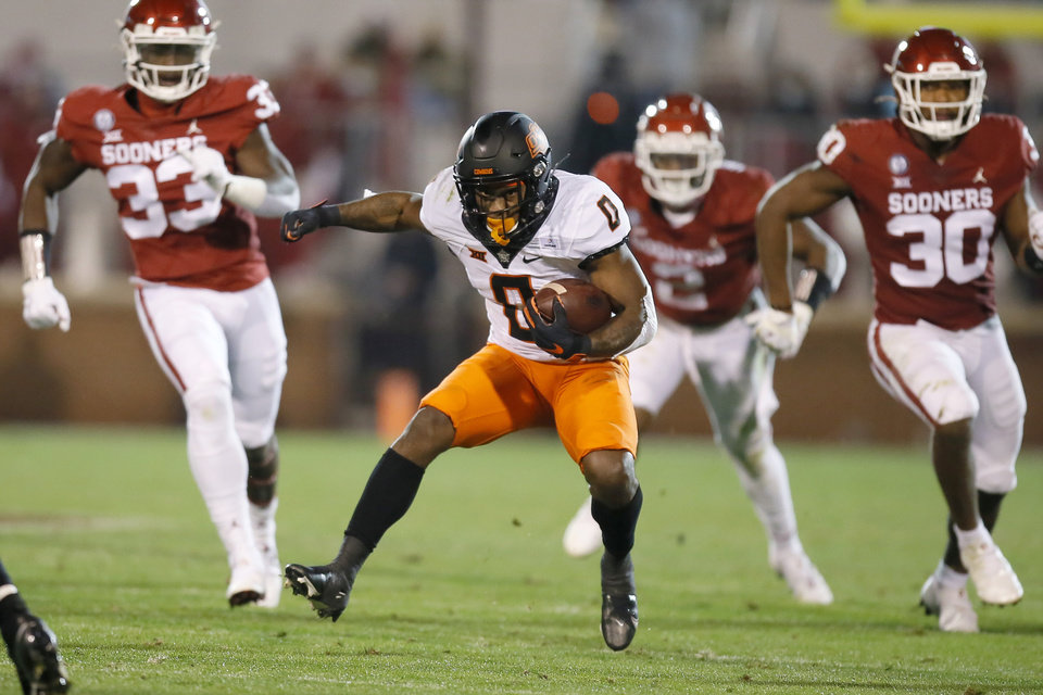 Photo - Oklahoma State's LD Brown (0) carries the ball during a Bedlam college football game between the University of Oklahoma Sooners (OU) and the Oklahoma State Cowboys (OSU) at Gaylord Family-Oklahoma Memorial Stadium in Norman, Okla., Saturday, Nov. 21, 2020. Oklahoma won 41-13. [Bryan Terry/The Oklahoman]