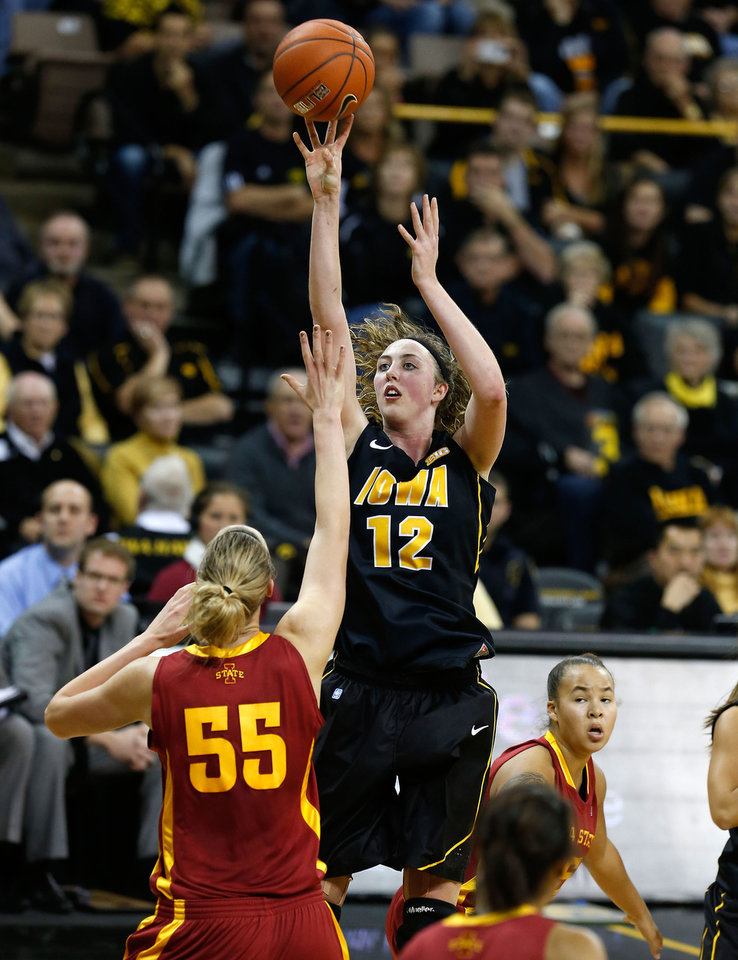 Photo - Iowa center Morgan Johnson (12) puts up a shot over Iowa State center Anna Prins (55) during the first half an NCAA college basketball game Thursday, Dec. 6, 2012 at Carver-Hawkeye Arena in Iowa City, Iowa.  (AP Photo/The Gazette,Brian Ray)