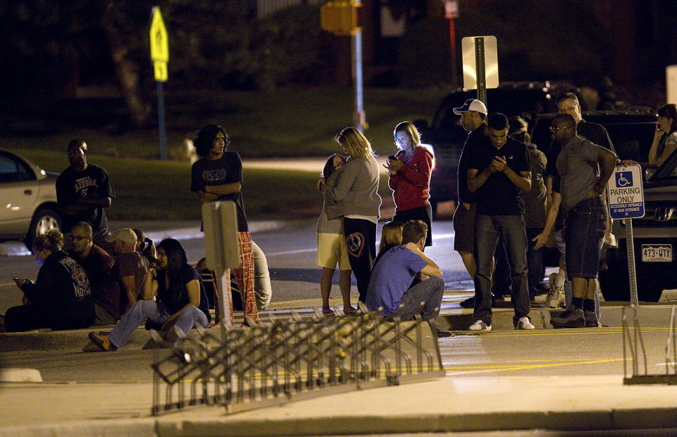 Photo - Family and friends wait outside Gateway High School where witnesses were brought for questioning after a shooting at a movie theater showing the Batman movie