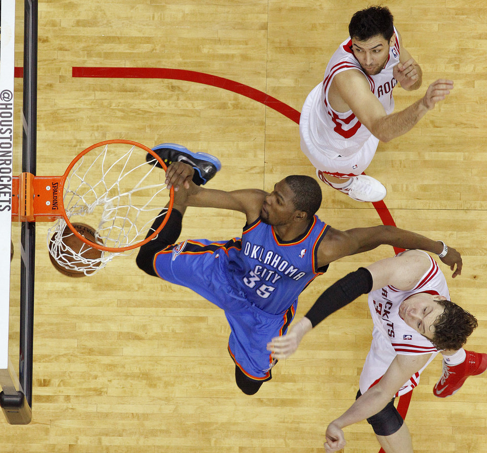 Oklahoma City\'s Kevin Durant (35) goes between Houston\'s Carlos Delfino (10) and Omer Asik (3) for a dunk during Game 4 in the first round of the NBA playoffs between the Oklahoma City Thunder and the Houston Rockets at the Toyota Center in Houston, Texas,Sunday, April 29, 2013. Oklahoma City lost 105-103. Photo by Bryan Terry, The Oklahoman