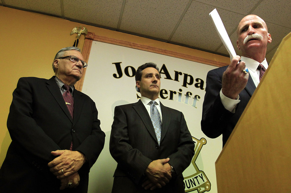 Photo -   Maricopa County Sheriff Joe Arpaio, left, and one of his attorney's Joseph Popolizio, middle, listen to another attorney, John Masterson, as he holds up a copy of the civil rights lawsuit handed out by the Department of Justice today, as he answers questions regarding the federal civil rights lawsuit against Sheriff Arpaio and his department, during a news conference Thursday, May 10, 2012, in Phoenix. According to the Department of Justice, after months of negotiations failed to yield an agreement to settle allegations that the sheriff's department racially profiled Latinos in his trademark immigration patrols, the lawsuit was filed.(AP Photo/Ross D. Franklin)