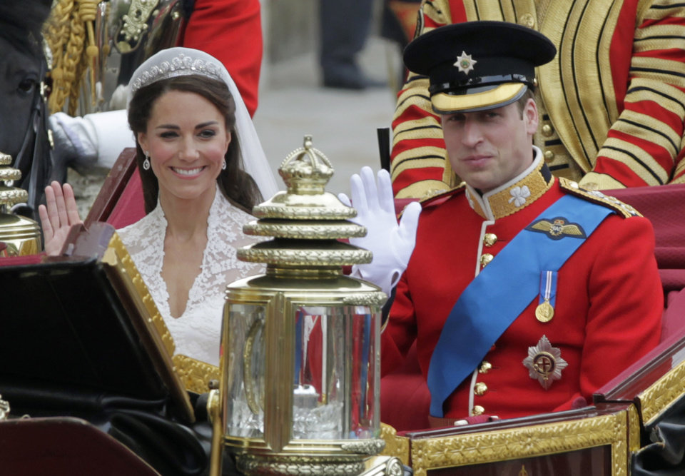 Photo - Britain's Prince William and his wife Kate, Duchess of Cambridge, left, wave as they leave Westminster Abbey at the Royal Wedding in London Friday, April 29, 2011. (AP Photo/Alastair Grant)  ORG XMIT: RWFO143