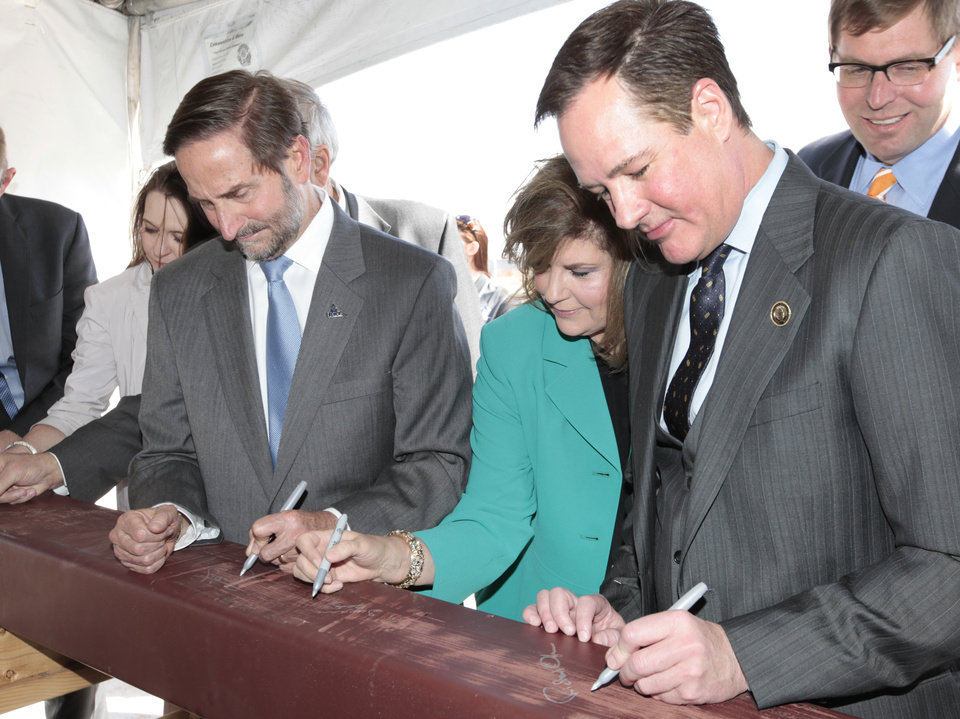 Photo -  University of Central Oklahoma President Don Betz, his wife Susanne, and Regional University System of Oklahoma Regent Richard Ogden sign a beam during a ceremony Thursday celebrating the start of construction on the Central Boathouse. Photo by David McDaniel, The Oklahoman   David McDaniel -
