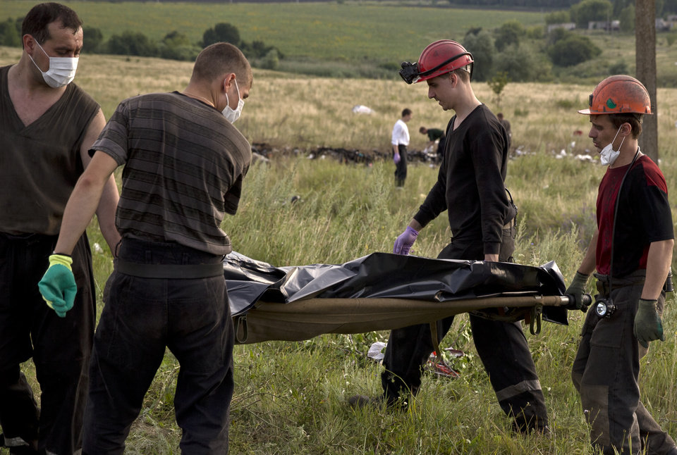 Photo - Ukrainian miners carry the body of a victim at the crash site of Malaysia Airlines Flight 17 near the village of Hrabove, eastern Ukraine, Saturday, July 19, 2014. World leaders demanded Friday that pro-Russia rebels who control the eastern Ukraine crash site of Malaysia Airlines Flight 17 give immediate, unfettered access to independent investigators to determine who shot down the plane. (AP Photo/Vadim Ghirda)