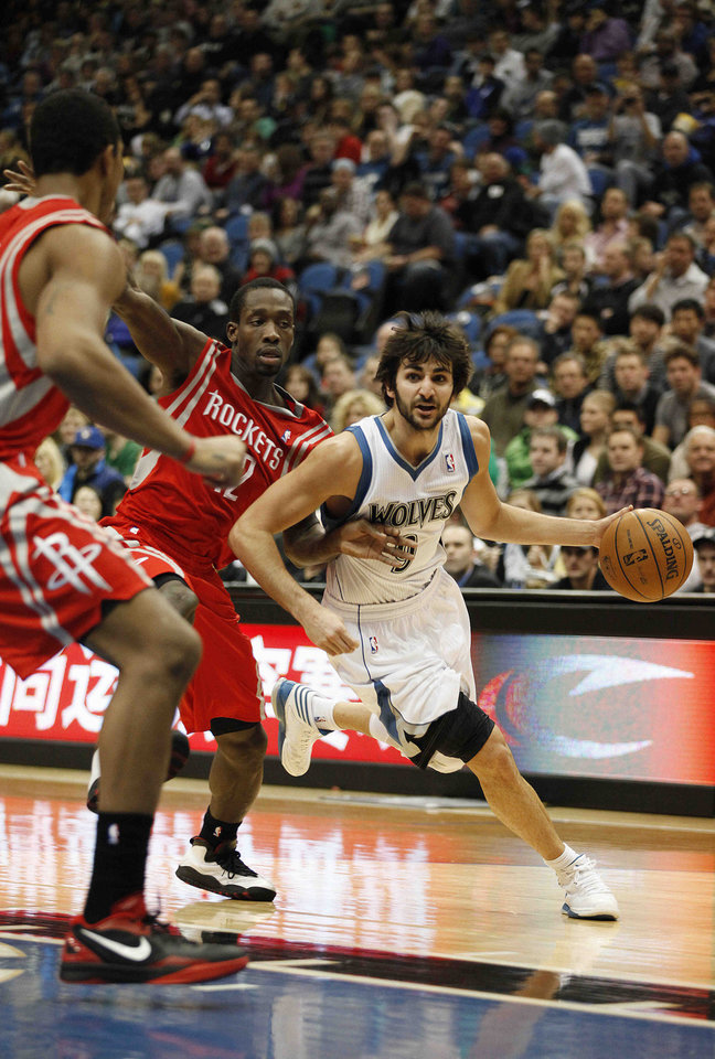 Photo - Minnesota Timberwolves guard Ricky Rubio (9) drives the ball past Houston Rockets guard Patrick Beverley (12) in the first half of an NBA basketball game on Saturday, Jan. 19, 2013, in Minneapolis. (AP Photo/Stacy Bengs)