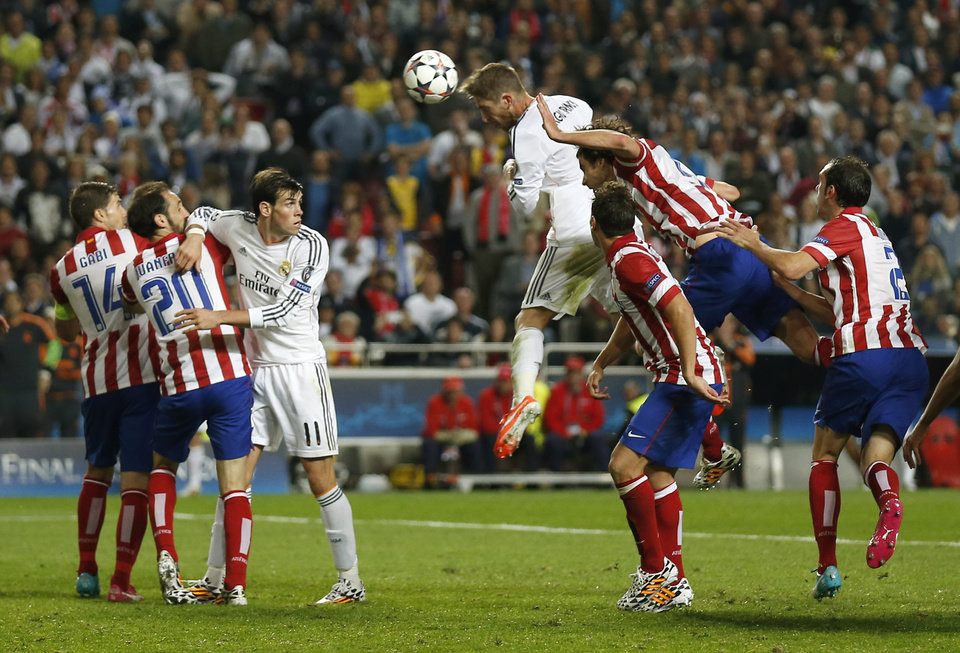 Photo - Real Madrid's Sergio Ramos, center, scores his side's first goal during the Champions League final soccer match against Atletico Madrid at the Luz Stadium in Lisbon, Portugal, Saturday, May 24, 2014. (AP Photo/Andres Kudacki)