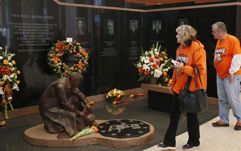 Photo - Oklahoma State University alumni Mary McCroskey, left, and Freddy McCroskey, right, of Oklahoma City, view the memorial to the the 10 men killed in the Jan. 27, 2001 Oklahoma State plane crash before the start of an NCAA college basketball game between West Virginia and Oklahoma State in Stillwater, Okla., Saturday, Jan. 25, 2014. (AP Photo/Sue Ogrocki)