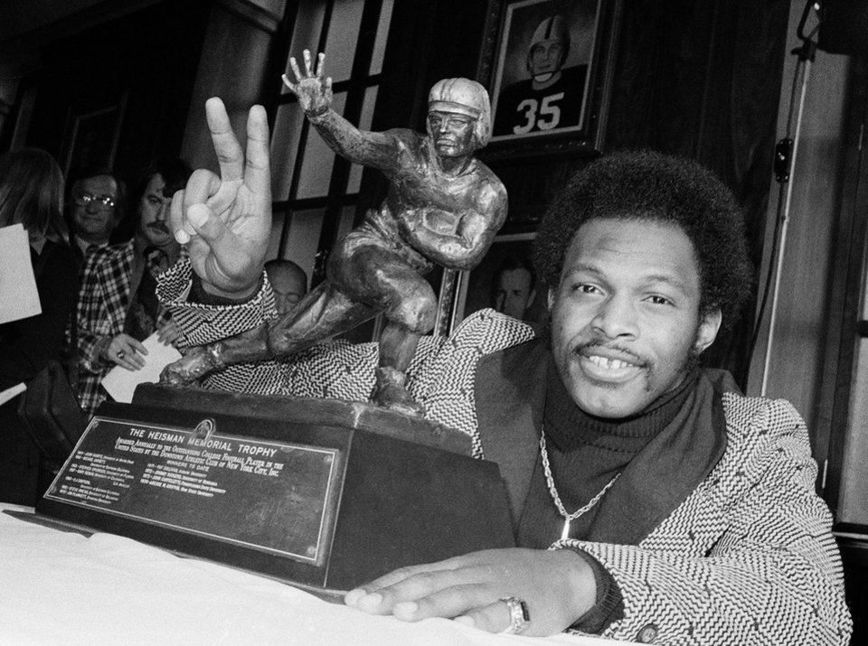 Photo - FILE - In this Dec. 2, 1975 file photo, Ohio State's running back Archie Griffin smiles and holds up two fingers as he poses with the 1975 Heisman Trophy in New York. Florida State quarterback Jameis Winston has the opportunity to accomplish what only one other player has achieved _ win consecutive Heisman trophies. Griffin won the award 1974 and 1975. He is shocked that he remains the lone repeat winner since the award's inception in 1935.   (AP Photo/File)