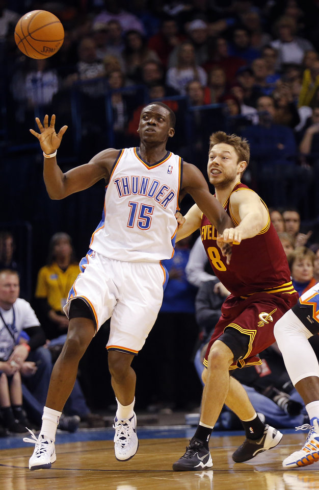 Photo - Cleveland's Matthew Dellavedova (8) ties to break up a pass to Oklahoma City's Reggie Jackson (15) during the NBA basketball game between the Oklahoma City Thunder and the Cleveland Cavaliers at the Chesapeake Energy Arena in Oklahoma City, Okla. on Wednesday, Feb. 26, 2014.  Photo by Chris Landsberger, The Oklahoman