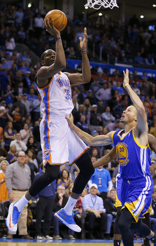 Photo - Oklahoma City's Kevin Durant (35) goes to the basket beside Golden State's Stephen Curry (30) during an NBA basketball game between the Oklahoma City Thunder and the Golden State Warriors at Chesapeake Energy Arena in Oklahoma City, Saturday, Jan. 18, 2014. Oklahoma City won 127-121. Photo by Bryan Terry, The Oklahoman