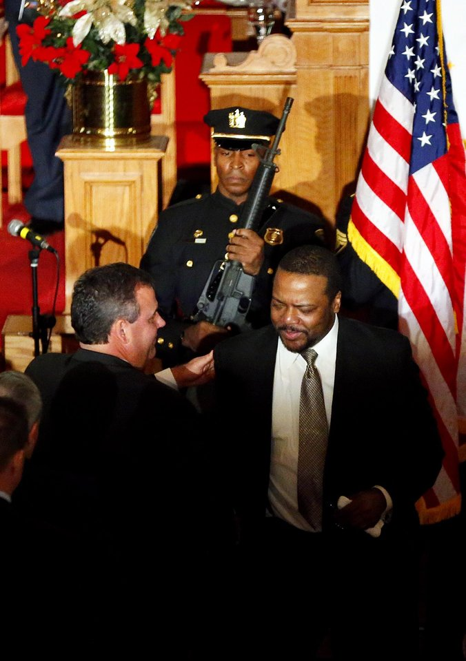 Photo - New Jersey Gov. Chris Christie shakes hugs Pastor Joe Carter after a prayer service in celebration of his inauguration at the New Hope Baptist Church on Tuesday, Jan. 21, 2014 in Newark. The celebrations to mark the start of Christie's second term could be tempered by investigations into traffic tie-ups that appear to have been ordered by his staff for political retribution and an allegation that his administration linked Superstorm Sandy aid to approval for a real estate project. (AP Photo/Rich Schultz)