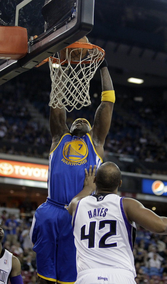 Photo - Golden State Warriors center Jermaine O'Neal, left, goes for a shot over Sacramento Kings forward Chuck Hayes during the first quarter of an NBA basketball game in Sacramento, Calif., Sunday, Dec. 1, 2013. (AP Photo/Rich Pedroncelli)