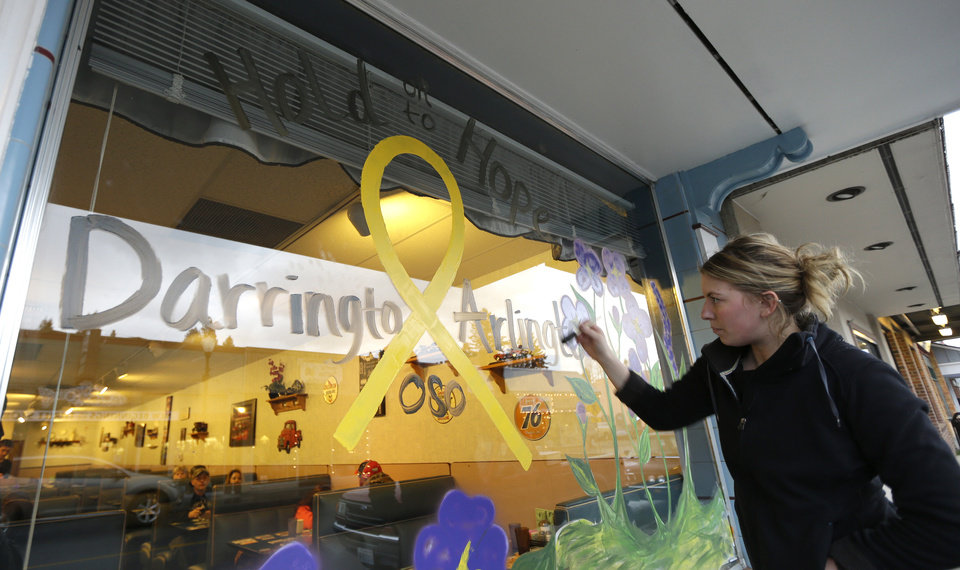 Photo - Jammi Parris, a waitress at the Blue Bird Cafe in downtown Arlington, Wash., paints a yellow ribbon and the words