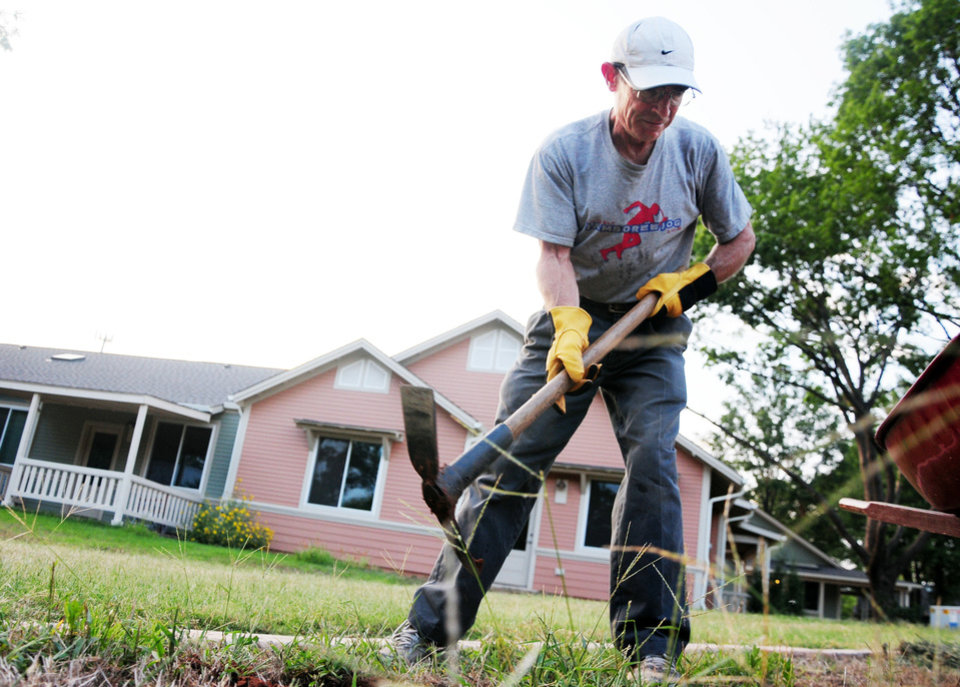 Photo - Mike Kelly, a family doctor in Stillwater with experience throughout the world and a resident of Oakcreek Cohousing Community, digs holes to place plants in to create a pathway on Sept. 12, 2013 in Stillwater, Okla. Residents share community responsibilites like yard work and general maintenance of the grounds. Photo by KT King/For the Oklahoman