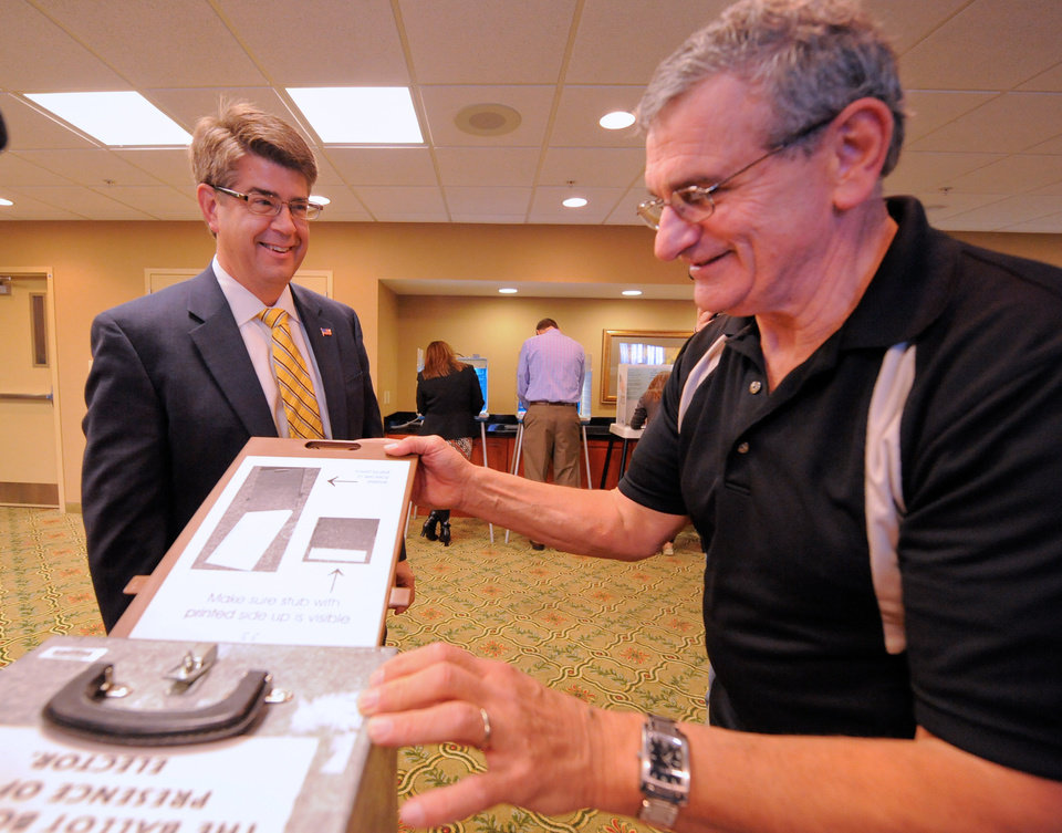 Nebraska Congressman Lee Terry watches Jerry King drop his ballot into a lock box, Tuesday Nov 6, 2012 while voting in Omaha, Neb. After a grinding presidential campaign, Americans head into polling places across the country. (AP Photo/Dave Weaver)