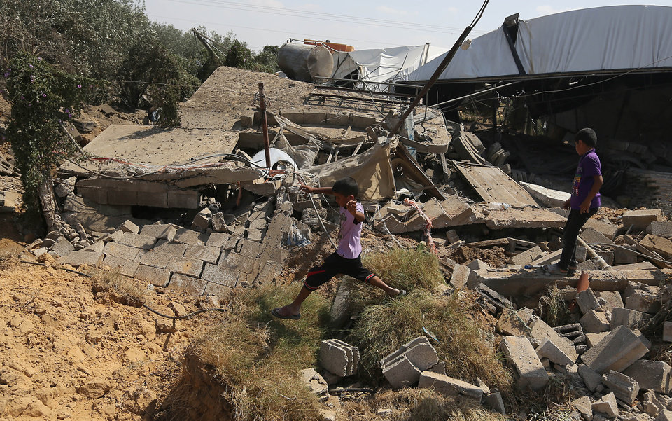 Photo - Palestinians inspect the rubble of a house after it was hit by an Israeli missile strike in Rafah, southern Gaza Strip, Sunday, July 6, 2014. The Israeli airstrikes targeted what the army said were militant sites including rocket launchers and a weapons manufacturing site, following at least 29 other rockets and mortar shells fired from the Gaza Strip at Israel over the weekend.(AP Photo/Hatem Moussa)