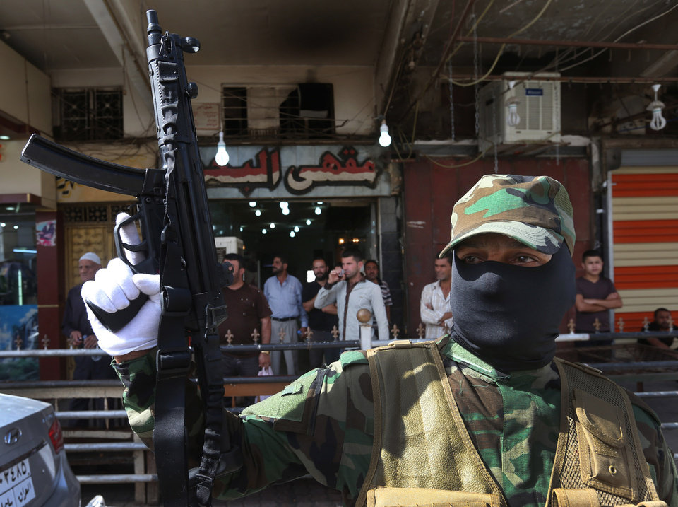 Photo - An Iraqi Shiite masked militiaman, a follower of Shiite cleric Muqtada al-Sadr, holds up his machine gun during a parade in the northern oil rich province of Kirkuk, Iraq, Saturday, June 21, 2014. Thousands of heavily-armed Shiite militiamen paraded through several Iraqi cities on Saturday as Sunni militants seized two strategically located towns in what appeared to be a new offensive in the western Anbar province. (AP Photo/Hussein Malla)