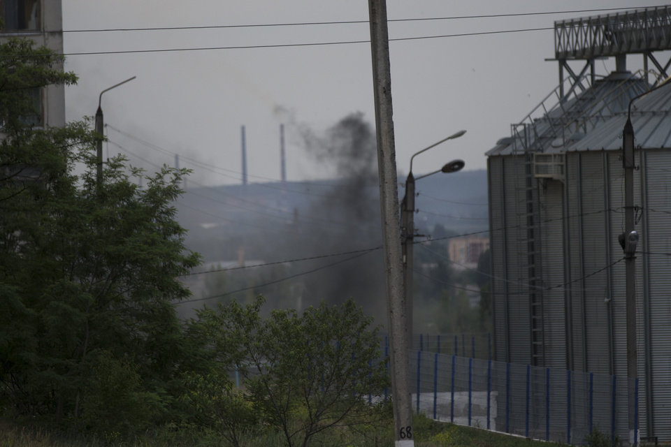 Photo - Smoke rises from a nearby explosion following a shelling from Ukrainian government forces in Slovyansk, Ukraine, Monday, May 26, 2014.  Exit polls from Sunday's first round of the new presidential election predict Petro Poroshenko will be elected president in this bitterly divided country, and he vowed
