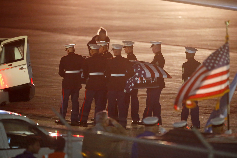 Photo -  Members of the U.S. Marines Honor Guard carrying the casket containing the remains of Marines Pvt. Vernon Keaton from the airplane to the hearse at Will Rogers World Airport on Tuesday night. [Photo by Bryan Terry, The Oklahoman]