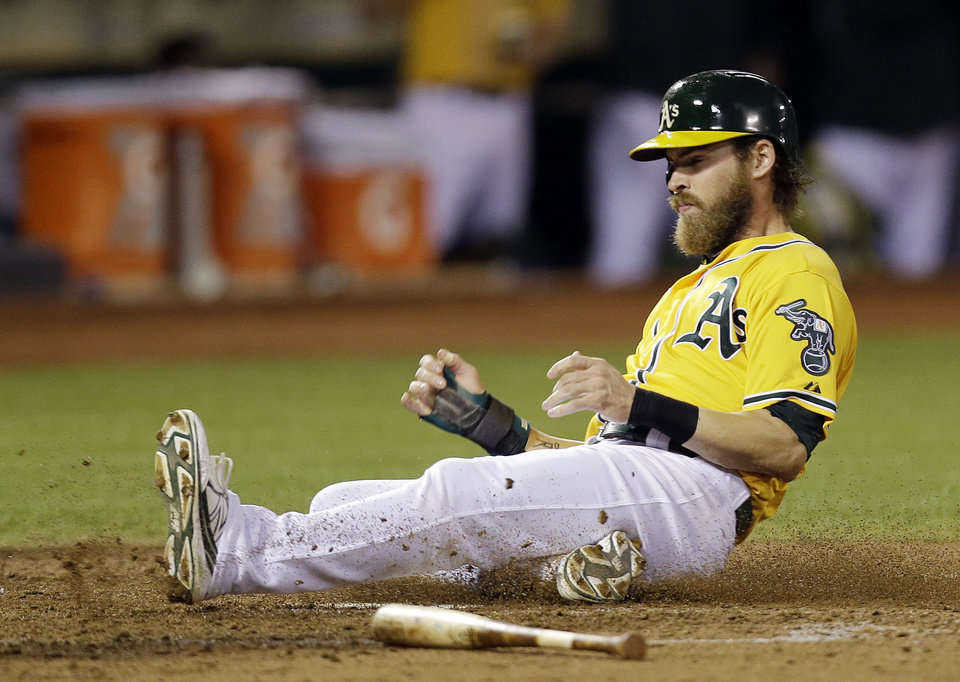 Oakland Athletics\' Josh Reddick scores on a sacrifice fly by Stephen Vogt during the fourth inning of a baseball game against the Minnesota Twins on Thursday, Sept. 19, 2013, in Oakland, Calif. (AP Photo/Marcio Jose Sanchez)