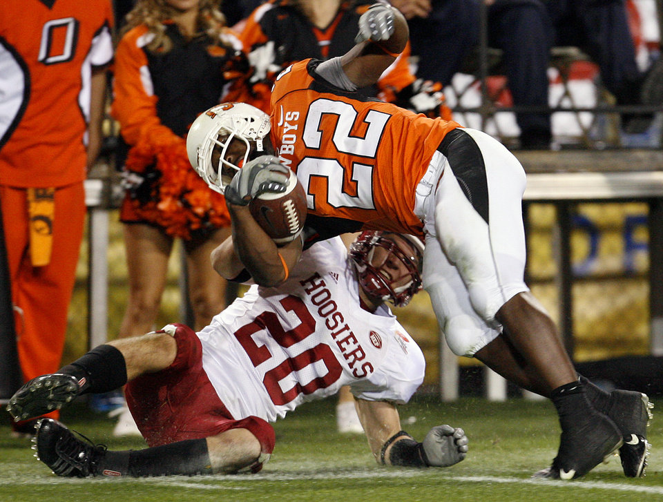 Photo - Indiana's Austin Thomas (20) drags down Oklahoma State's Dantrell Savage (22) during second half of the Insight Bowl college football game between Oklahoma State University (OSU) and the Indiana University Hoosiers (IU) at Sun Devil Stadium on Monday, Dec. 31, 2007, in Tempe, Ariz.   BY BRYAN TERRY, THE OKLAHOMAN ORG XMIT: KOD