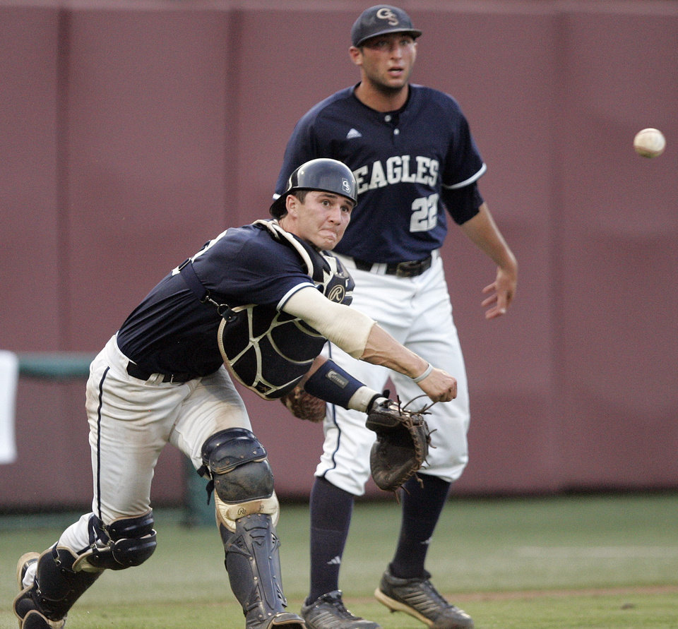 Photo - Georgia Southern catcher Max Pentecost, left, throws out a Kennesaw State runner as relief pitcher Jason Richman looks on in the fifth inning of an NCAA regional college baseball game on Saturday, May 31, 2014, in Tallahassee, Fla. (AP Photo/Steve Cannon)