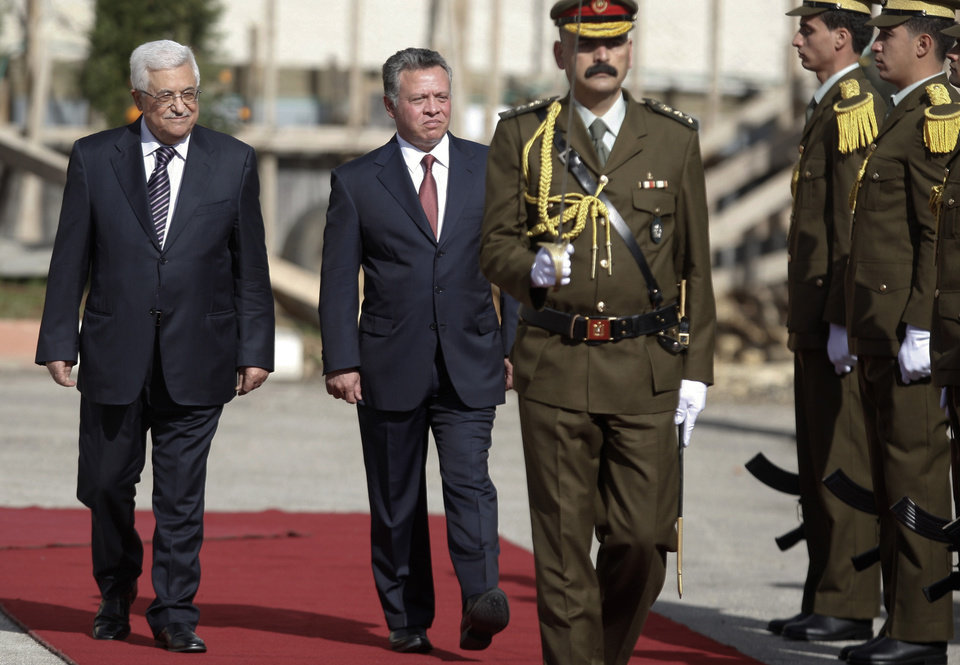 King Abdullah II of Jordan, center, and Palestinian President Mahmoud Abbas, left, walk past honor guards prior to their meeting in the West Bank city of Ramallah, Thursday, Dec. 6, 2012. Jordan's King Abdullah II has begun a brief visit to the West Bank in support of Palestinian President Mahmoud Abbas' successful bid for U.N. recognition of a state of Palestine. (AP Photo/Majdi Mohammed)