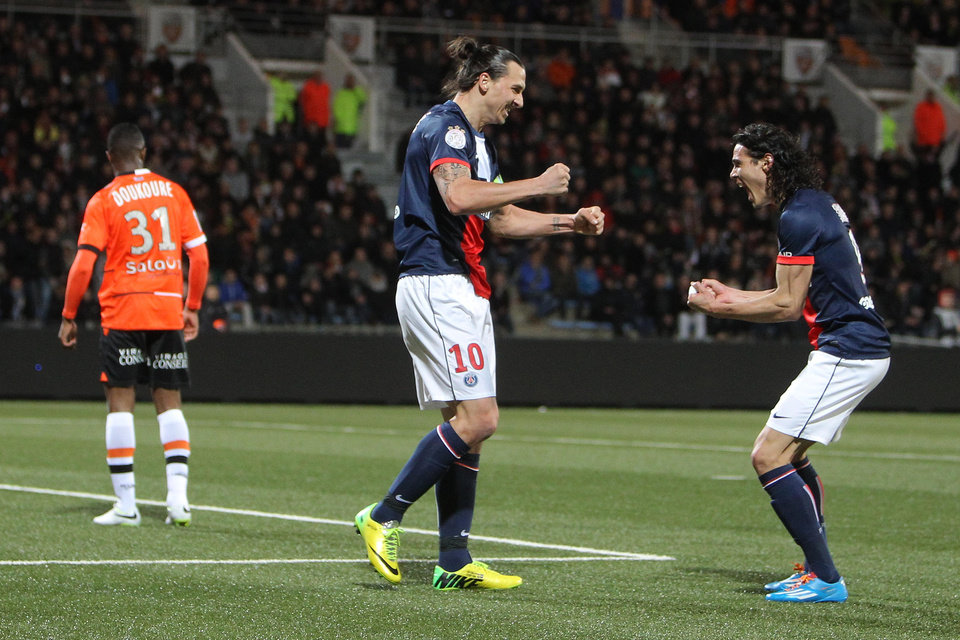 Photo - Paris Saint Germain's Zlatan Ibrahimovic, center, and Edison Cavanni, right, jubilate after the first goal during their French League one soccer match, in Lorient, western France, Friday, March 21, 2014. (AP Photo/David Vincent)