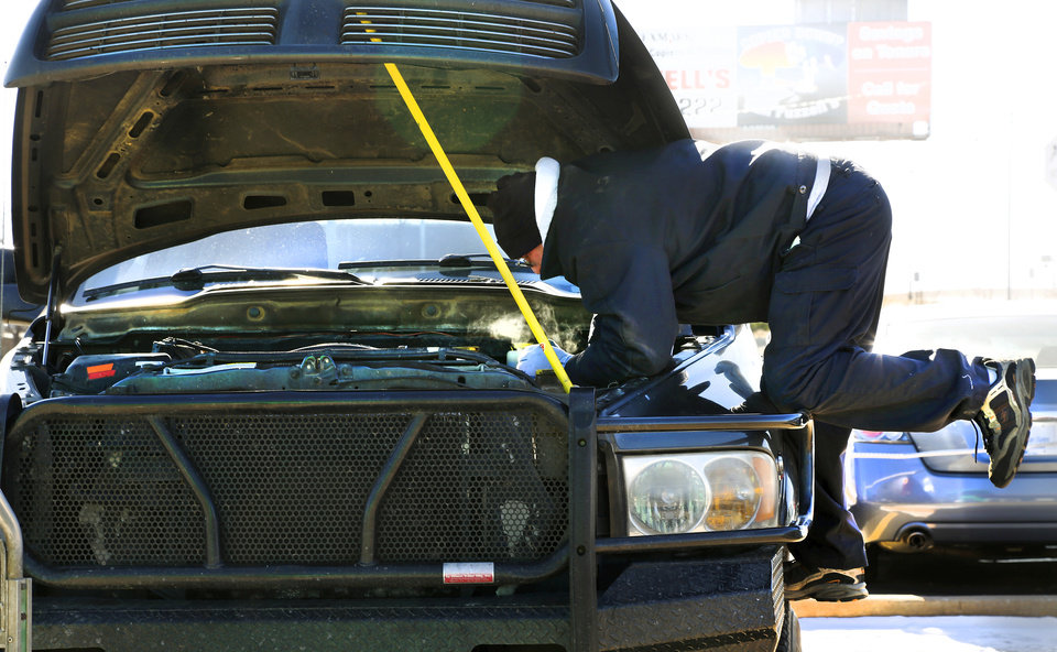 Photo - A mechanic climbs into the engine compartment of this pick-up truck to replace one of its two dead batteries at Interstate Batteries.  Many motorists found themselves dealing with the inconveniences created by frigid sub-freezing temperatures, part of a major winter storm that continues to grip much of the central sections and the eastern half of the United States. Photo taken Monday, Jan. 6, 2014.  Photo by Jim Beckel, The Oklahoman
