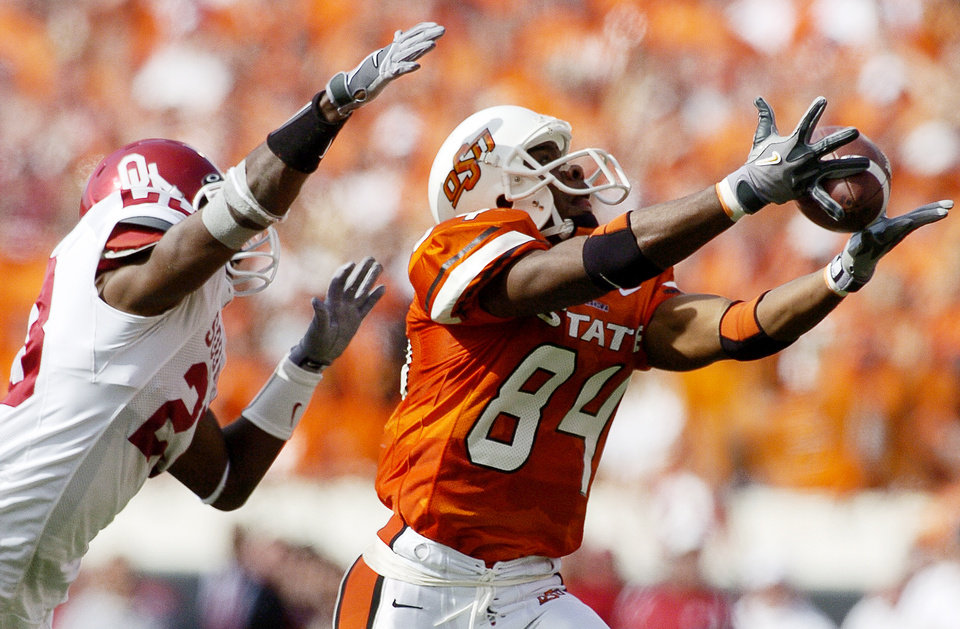 D'Juan Woods of OSU catches a pass for 32 yards in front of Brodney Pool of OU during the University of Oklahoma at Oklahoma State University Bedlam college football at Boone Pickens Stadium in Stillwater, Okla., October 30, 2004. By Bryan Terry/The Oklahoman