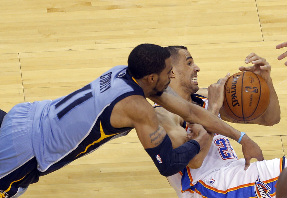 Photo - Oklahoma City's Thabo Sefolosha (25) and Memphis' Mike Conley wrestles for a loose ball during Game 2 in the first round of the NBA playoffs between the Oklahoma City Thunder and the Memphis Grizzlies at Chesapeake Energy Arena in Oklahoma City, Monday, April 21, 2014. Photo by Sarah Phipps, The Oklahoman