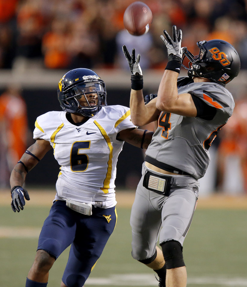 Photo - Oklahoma State's Austin Hays (84) catches a pass beside West Virginia's Pat Miller (6) during a college football game between Oklahoma State University (OSU) and West Virginia University at Boone Pickens Stadium in Stillwater, Okla., Saturday, Nov. 10, 2012. Oklahoma State won 55-34. Photo by Bryan Terry, The Oklahoman