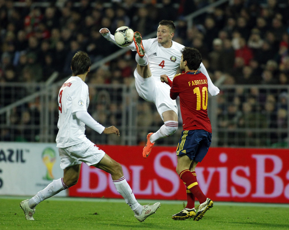 Photo -   Spain's Francesc Fabregas, right, vies for the ball with Belarus' Igor Shitov, center, an Aleksandr Martynovich during a World Cup 2014 Group qualification match between Belarus and Spain national teams in Minsk, Belarus, on Friday, Oct. 12, 2012.(AP Photo/Sergei Grits)