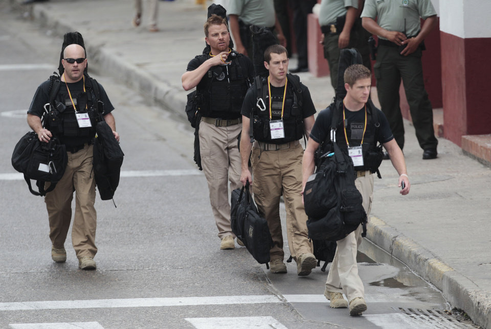 Photo -   U.S. secret service agents walk around the Convention Center in Cartagena, Colombia, prior to the opening ceremony of the 6th Summit of the Americas at the Convention Center in Cartagena, Colombia, Saturday, April 14, 2012. Last Thursday, a dozen secret service agents sent to provide security for U.S. President Barack Obama, were relieved from duty and replaced with other agency personnel after an incident of alleged misconduct. (AP Photo/Fernando Llano)