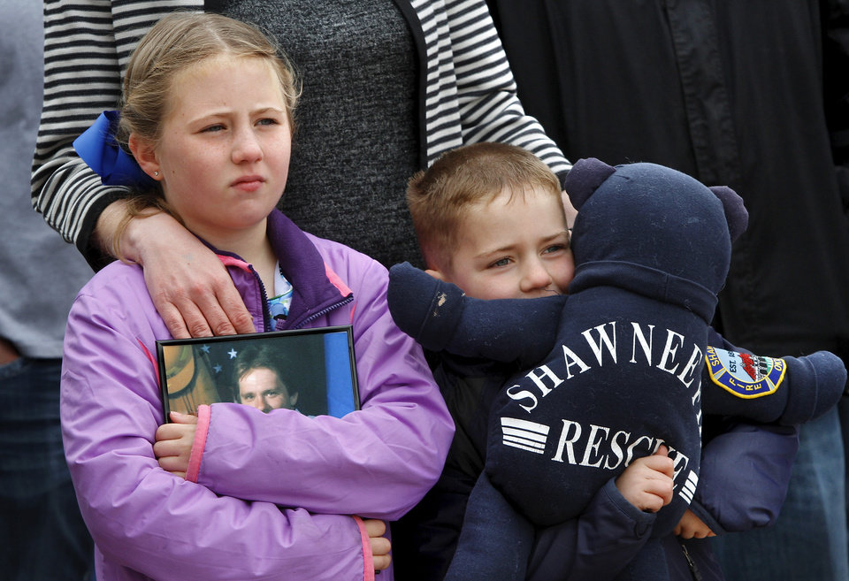 CHILD / CHILDREN / KIDS / RICHARD TREECE: Cadence Treece, 7, cradles a photo of her dad, Lt. Wesley Treece,  a lieutenant with 14 years of service in the Shawnee Fire Department before dying from colon cancer  in March, 2009.  Treece was 42. Beside her is her brother, Richard, 6, who hugs a large stuffed bear. Lt. Treece was among hundreds   of firefighters who responded to the scene in Oklahoma City after the Alfred P. Murrah Federal Building was destroyed in the bombing on April, 19, 1995. The children attended the rally with their mother, Richelle (cq). An estimated 400 active and retired firefighters from across Oklahoma rallied on the south plaza of the state Capitol Monday morning, March 18, 2013, before going inside the building to visit with lawmakers and voice their concerns about proposed changes in pension and workers' compensation system.      Photo by Jim Beckel, The Oklahoman