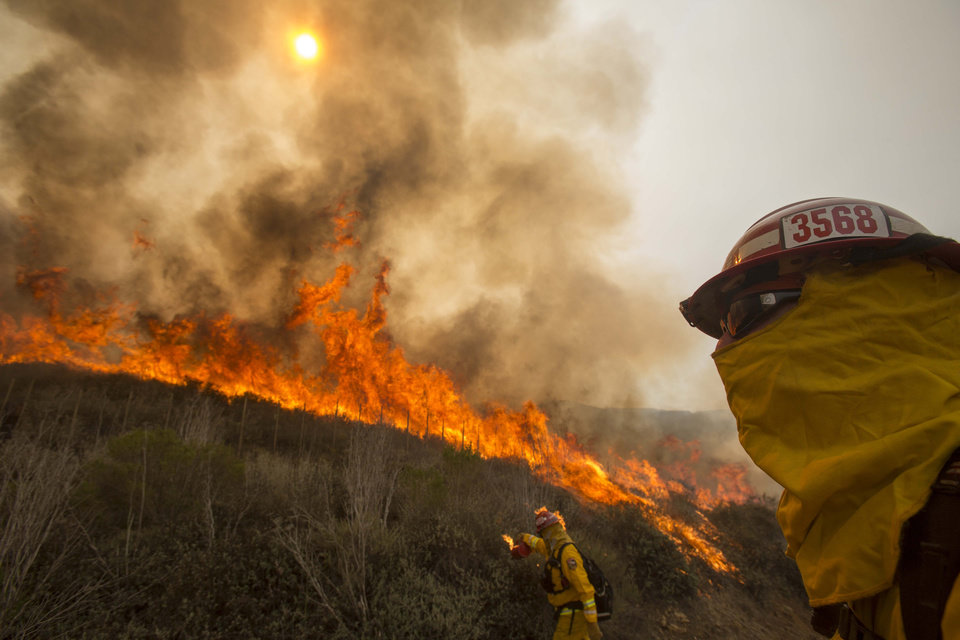 Photo - A firefighter watches a wildfire along a hillside in Point Mugu , Calif. Friday, May 3, 2013. Firefighters got a break as gusty winds turned into breezes, but temperatures remained high and humidity levels are expected to soar as cool air moved in from the ocean and the Santa Ana winds retreated. (AP Photo/Ringo H.W. Chiu)