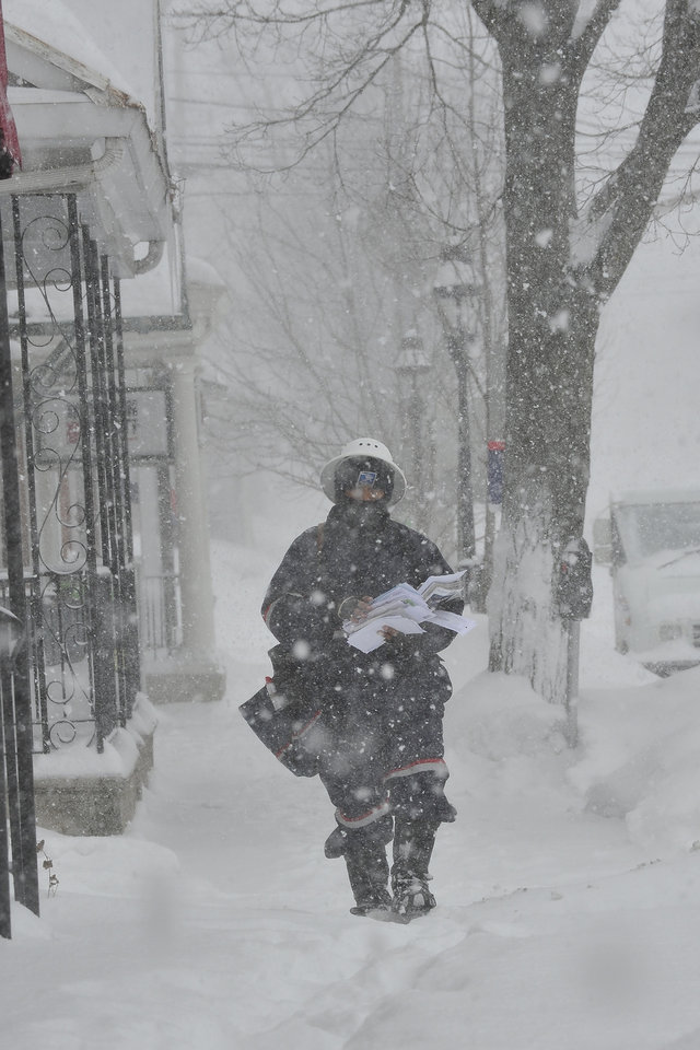Photo - Mailman Simeon Reed makes his mail delivery rounds through deep snow and blizzard conditions on Broad Street in Bethlehem, Pa. on Thursday, Feb. 13, 2014. The storm spread heavy snow and sleet along the Northeast corridor. (AP Photo/Chris Post)