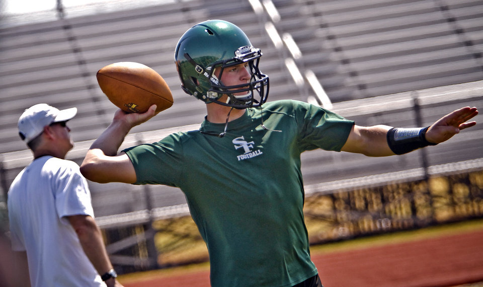 Photo - Edmond Santa Fe quarterback Justice Hansen takes to the field during the first day of football practice at Edmond Santa Fe High School on Tuesday, Aug. 7.  Photo by Chris Landsberger, The Oklahoman