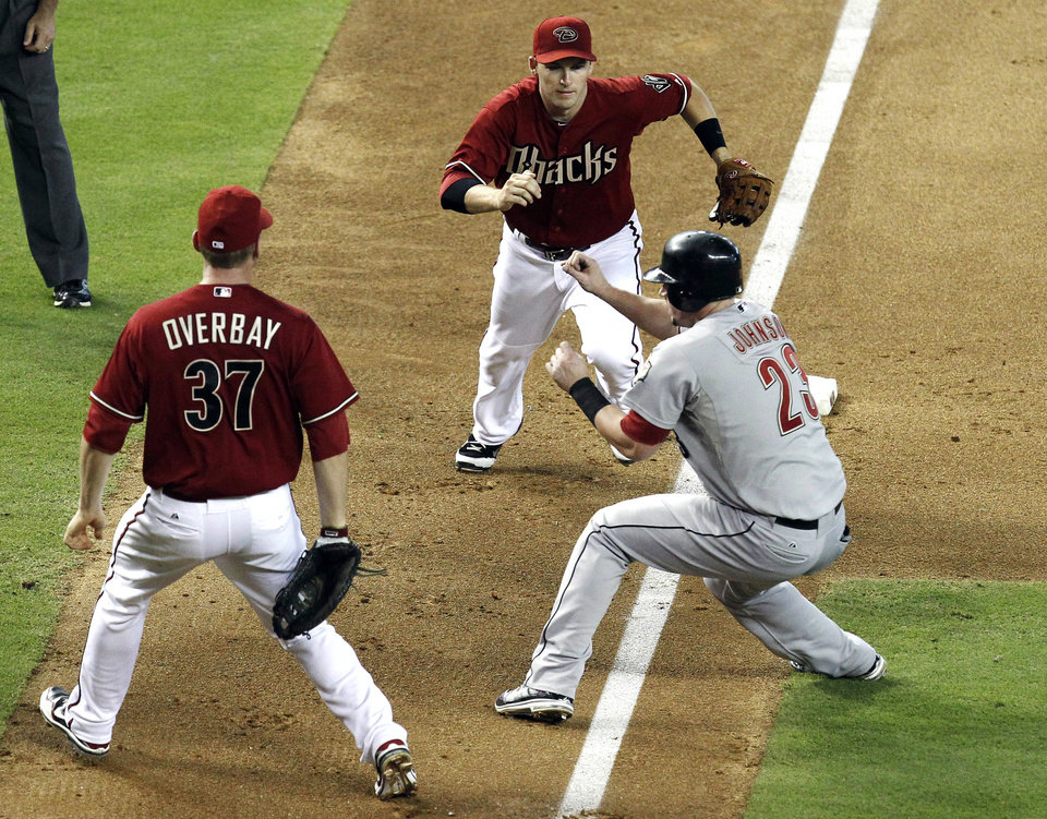 Photo -   Houston Astros' Chris Johnson (23) gets caught in a rundown between Arizona Diamondbacks' Lyle Overbay (37) and Stephen Drew, who would eventually tag Johnson out, in the sixth inning during a baseball game, Sunday, July 22, 2012, in Phoenix. (AP Photo/Ross D. Franklin)