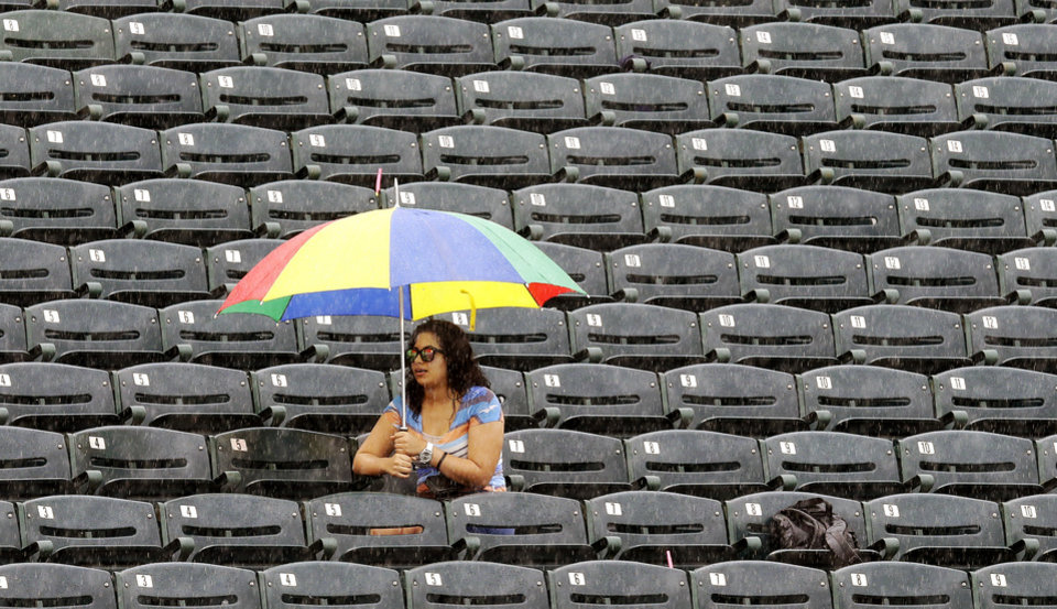 Photo - A fan waits out a rain delay in the stands at Hammond Stadium in the fifth inning of an exhibition spring training baseball game between the Minnesota Twins and the Miami Marlins in Fort Myers, Fla., Monday, March 18, 2013. (AP Photo/Elise Amendola)