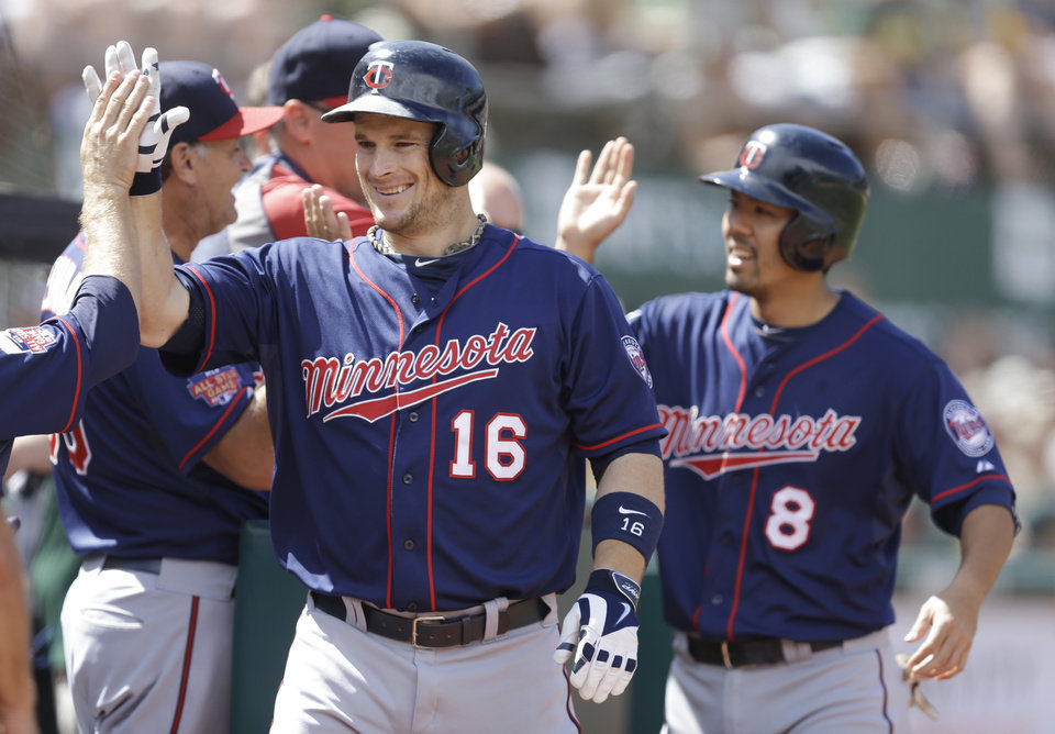 Photo - Minnesota Twins' Josh Willingham (16) is congratulated after hitting a two-run home run off Oakland Athletics' Luke Gregerson in the eighth inning of a baseball game Sunday, Aug. 10, 2014, in Oakland, Calif. (AP Photo/Ben Margot)