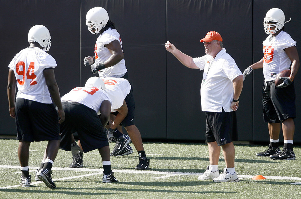 Photo - New OSU defensive coordinator Bill Young gives instructions during the Cowboys' practice Wednesday at Boone Pickens Stadium in Stillwater. (Photo by Bryan Terry, The Oklahoman)