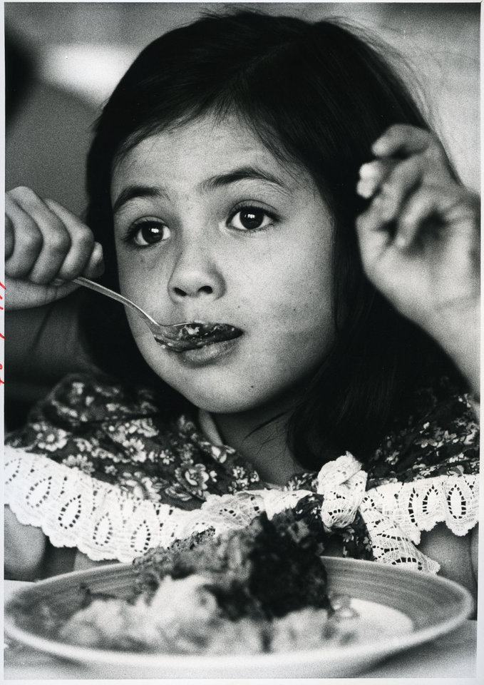 Photo - A young girl eats dinner at the Jesus House with her family in this 1983 photograph.   JIM BECKEL - STAFF