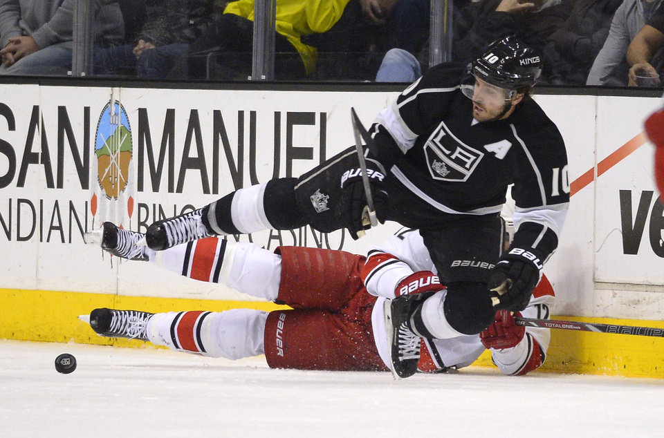 Photo - Los Angeles Kings center Mike Richards, top, and Carolina Hurricanes center Eric Staal vie for the puck during the second period of an NHL hockey game, Saturday, March 1, 2014, in Los Angeles. (AP Photo/Mark J. Terrill)