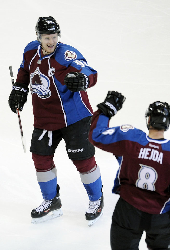 Photo - Colorado Avalanche left wing Gabriel Landeskog, left, of Sweden, congratulates Avalanche defenseman Jan Hejda, right, of the Czech Republic, after Hejda scored a goal in the first period of an NHL hockey game against the Ottawa Senators on Wednesday, Jan. 8, 2014, in Denver. (AP Photo/Chris Schneider)