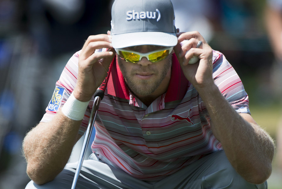 Photo - Graham DeLaet checks his line while on the second green during the third round of play at the Canadian Open golf championship in Montreal on Saturday, July 26, 2014. (AP Photo/The Canadian Press, Paul Chiasson)